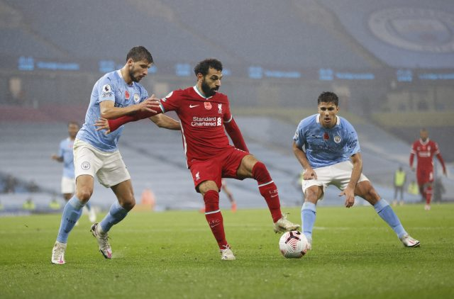 MANCHESTER, ENGLAND - NOVEMBER 08: Mohamed Salah of Liverpool holds off Ruben Dias of Manchester City during the Premier League match between Manchester City and Liverpool at Etihad Stadium on November 08, 2020 in Manchester, England. Sporting stadiums around the UK remain under strict restrictions due to the Coronavirus Pandemic as Government social distancing laws prohibit fans inside venues resulting in games being played behind closed doors. (Photo by Clive Brunskill/Getty Images)